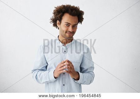 Attractive Young Afro-american Employee With Stubble And Stylish Haircut Standing At Blank Wall, Kee