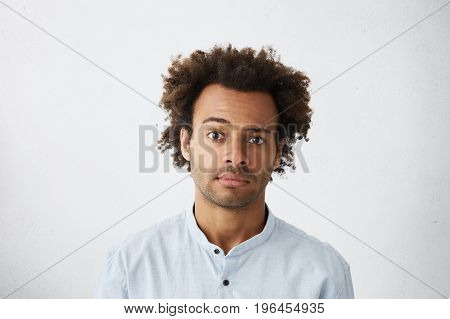 Handsome Sceptical Unshaven African American Office Worker Wearing Blue Shirt Posing In Studio Raisi