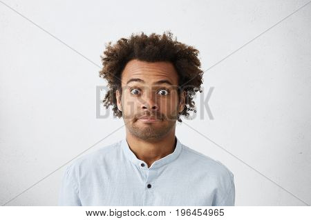 Human Facial Expressions And Emotions. Portrait Of Funny Bug-eyed Young Dark-skinned Student, Worker