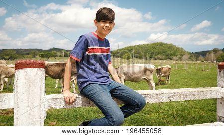 Portrait Of Happy Boy In Farm With Cows In Ranch