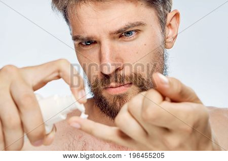 Young guy with beard on white isolated background applies cosmetic cream.