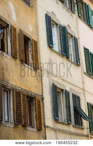 Facade Of An Old House In Florence With Weathered Wooden Window Shutters
