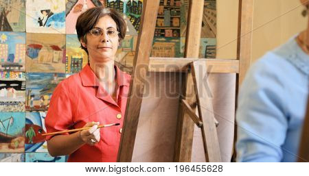 Elderly people painting for hobby. Portrait of happy old woman smiling looking at camera while practicing with brushes and canvas in school.