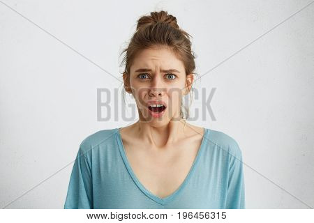 Offended And Dissatisfied Young Female Looking With Opened Mouth At Camera Complaining About Somethi