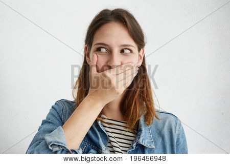 Pretty Female Covering Her Mouth While Giggling Looking Aside Posing Against White Studio Background