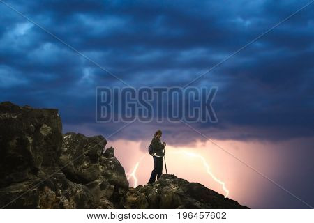 Lonely female trekker admiring mountain view from the top during lightening storm
