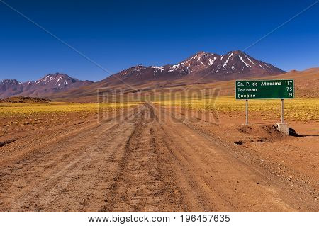 Dirt road with a road sign and mountains in the background in the Atacama Desert Chile; Concept for travel in Chile
