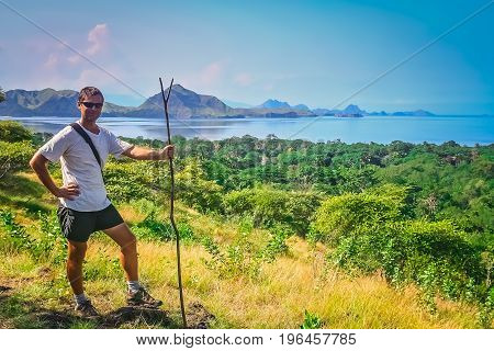 Trekker with a primitive walking stick replacement standing on a hill on the Komodo island, Indonesia
