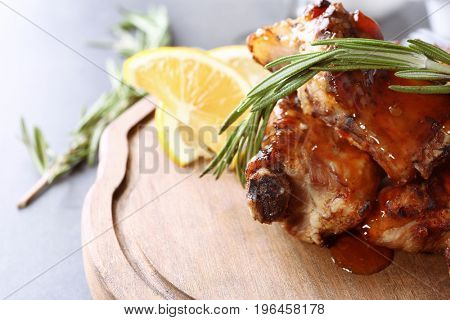 Delicious pork ribs with rosemary and lemon slices on wooden board, closeup