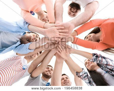 Group of young volunteers standing in circle and holding their hands together on white background
