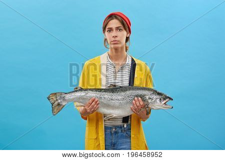 Young Fisherwoman Wearing Red Hat, Yellow Raincoat And Jean Overalls Holding Huge Fish Presenting He
