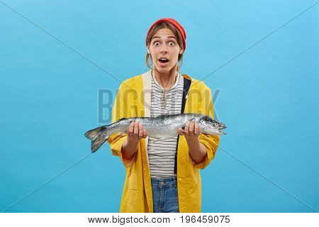 Astonished Fisherwoman Dressed Casually While Holding Big Fish Being Surprised To Catch So Huge Trou