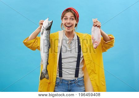 Cheerful Female Dressed In Red Hat And Yellow Raincoat Demonstrating Two Fish Which Her Husband Catc