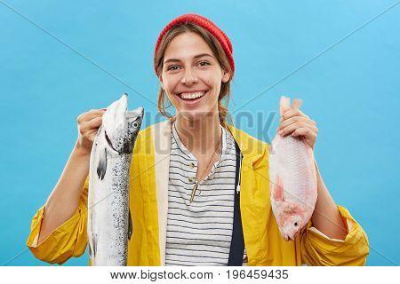 Studio Shot Of Attractive Young Wife Of Successful Fisherman Smiling Happily, Having Pleased And Che