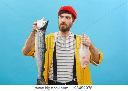 Serious Man With Blue Eyes And Thick Beard Wearing Red Hat And Yellow Raincoat Holding Two Fish Look
