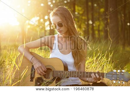 Beautiful Female With Long Luxurious Hair Wearing White Casual Shirt And Sunglasses Playing Acoustic