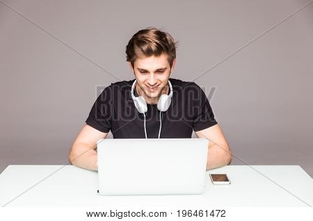 Happy Man Working In Front Of Laptop On Office Table