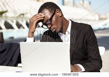 Tired Black Businessman In Black Suit And Eyewear Keeping Hand On Forehead While Sitting At Table Ou