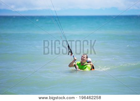 Male kite surfer showing young boy how to ride kite. Active family vacations concept.