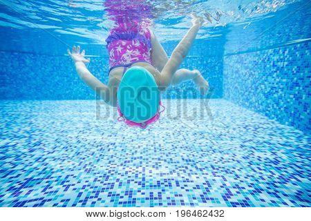 Little girl diving in indoor swimming pool