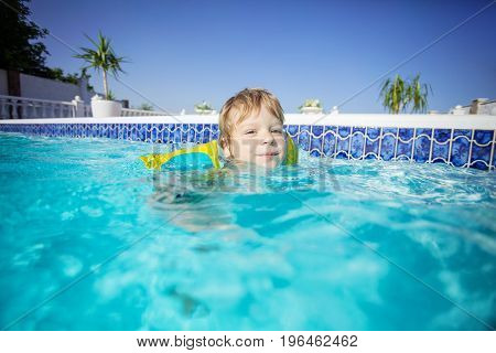 Happy blonde boy wearing floaties and swimming in outdoor pool