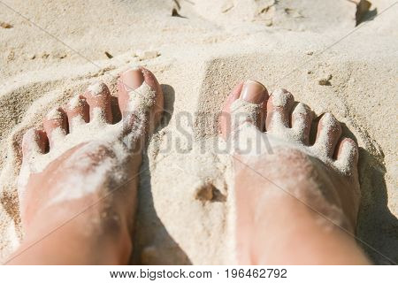 Close up of woman feet covered with white sand at the beach
