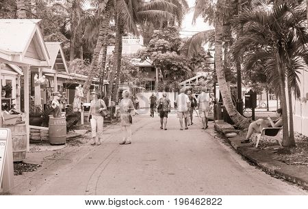Key West , Florida, USA - June 26, 2012; Tourist walk small palm tree lined Key West street with souvenir shops and bars in monochrome street scene.