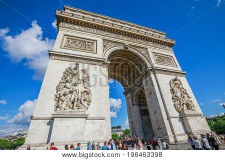 PARIS, FRANCE - JULY 2, 2017: Tourists under Arch of triumph. Arc de Triomphe at the western end of the Champs Elysees and at the center of Place Charles de Gaulle.