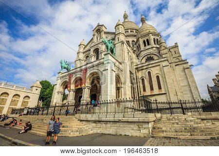 PARIS, FRANCE - JULY 3, 2017: left side view of the Sacred Heart Basilica of Paris in France in Montmartre historic district of Paris city in a blue cloudy sky with people during the morning mass.