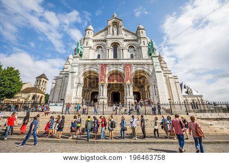PARIS, FRANCE - JULY 3, 2017: Central facade of Basilique du Sacre Coeur de Montmartre, Sacred Heart Church of Paris with tourists. Popular religious attraction in Paris.