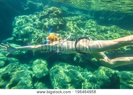 Female apnea bikini swims in tropical sea. Underwater background of a woman snorkeling and doing skin diving. Watersport activity in Europe. Tropical destination holiday concept.