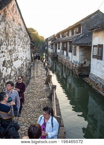 Suzhou, China - Nov 5, 2016: People on a peaceful narrow path of cobblestone at the historic Zhouzhuang Water Town. Path is along a water canal channel.