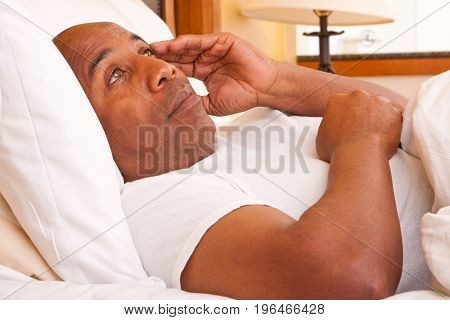 Mature African American man having trouble sleeping.