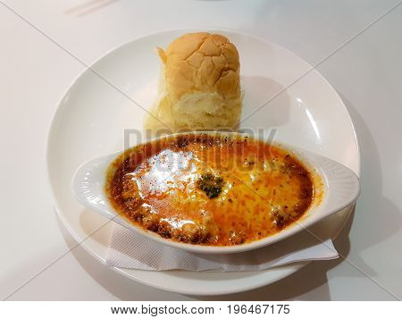 Background isolated still image of hot cheesy beef lasagne with bun on white tableware