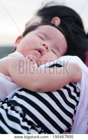 Mother holding her newborn baby in sexy dress while her was sleeping. Baby is sleeping on her mother shoulder at the rooftop. Mother day bonding concept with newborn baby nursing.