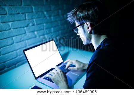 Man Using Laptop In The Night With White Screen. Young Hacker Work On Laptop In The Night