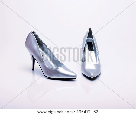 Silver high heels on a white background