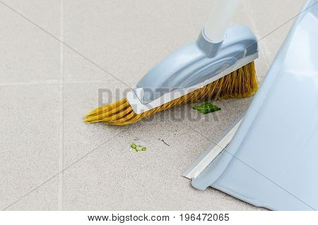 Smoothing leaves on a tile with a broom to a bucket
