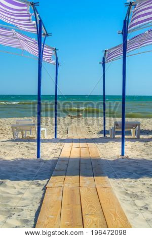 The path of wooden planks on the beach goes to the sea between the sun loungers