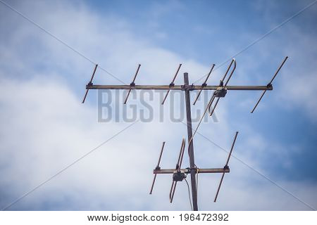 TV antenna on roof of house with blue sky background.