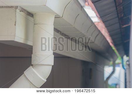 White stainless rain gutter on roof of house.