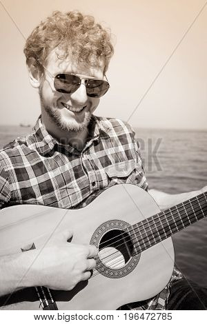 Happy young man hipster playing guitar by sea ocean water. Handsome guy in sunglasses relaxing on summer vacation.