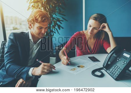 Business meeting between two co-workers: caucasian man employer in formal suit and businesswoman in red elegant dress sitting at oval table in office room and having dialogue about increase in profits