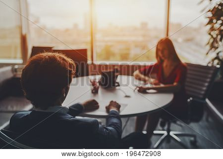 Office scene: company female employee is giving a report on work of her team to male boss in formal suit which is sitting with his back to camera in glass meeting room on high floor of skyscraper