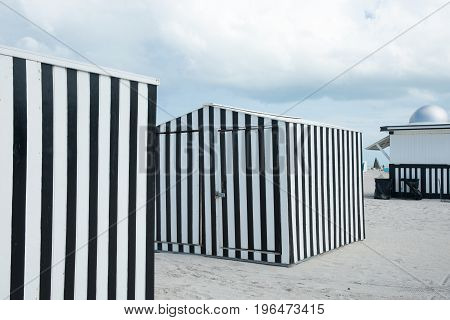 Striking black and white verticlly striped beack shed on beach Miami Florida