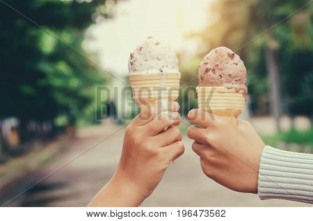 children's hands holding ice cream cone on summer light nature background