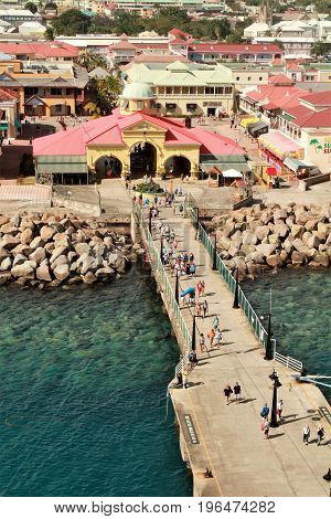 Port Zane cruise ship terminal on the island of St. Kitts - 3/8/2017 - cruise ship passengers walking down the dock to a cruise ship