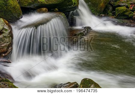 Small Cascade On The River Among Bouders In Forest