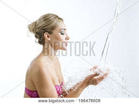 Beautiful girl posing in studio with water stream falling in her hands from above