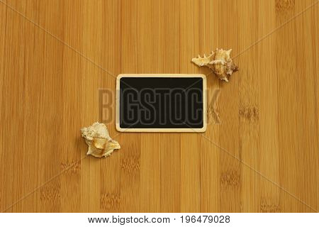 Small empty slate in width to write a message posed on the ground bamboo brown with beach shells on the sides
